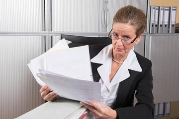 Chefin mit großem Papierstapel