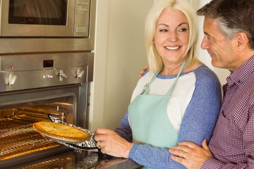 Woman taking fresh pie out of oven with husband