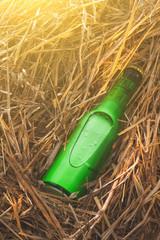 Beer bottle in the stack of hay