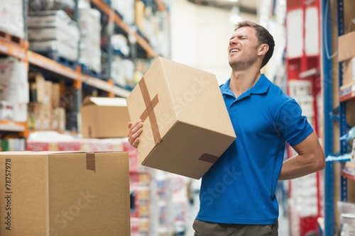 Leinwandbild Motiv Worker with backache while lifting box in warehouse