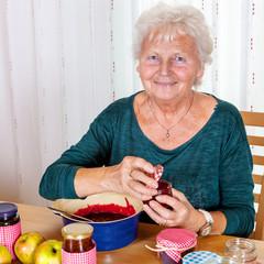 Senior woman filling homemade jam in the glass