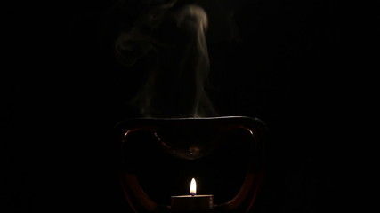 Candle Burns and Smoke Coming from the Oil Burner