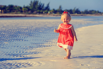 cute little girl walking on summer beach