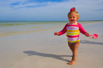 little girl playing on summer beach