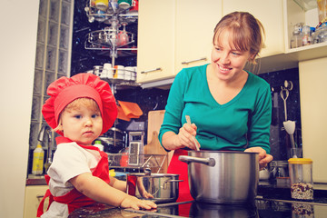 mother and little daughter cooking in the kitchen