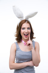 Portrait of laughing woman with bunny ears over gray background