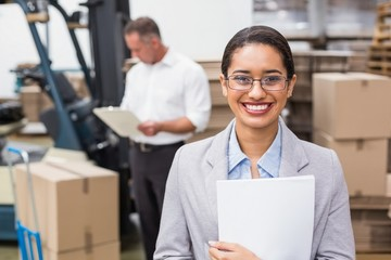 Female manager holding files during busy period
