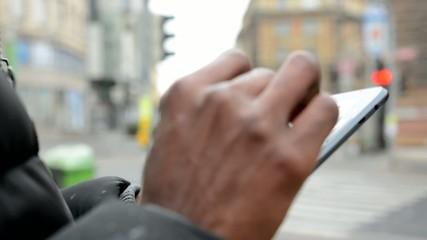 black man works on tablet - urban street - city - closeup