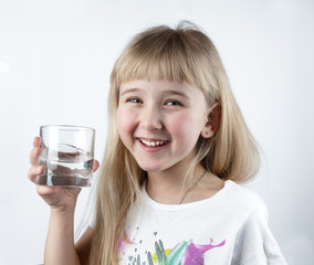 Little girl drinks water from a glass