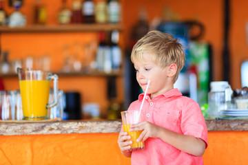 little boy drinking juice in cafe