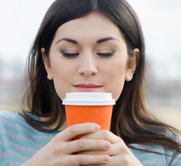 Woman with Coffee in a To-Go Cup outdoors.