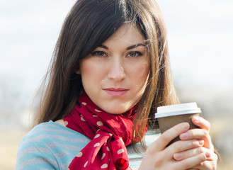 Woman with Coffee in a To-Go Cup.