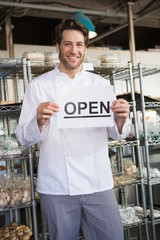 Portrait of a smiling baker holding open sign