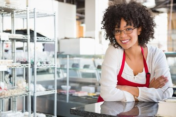 Smiling waitress with glasses leaning on counter