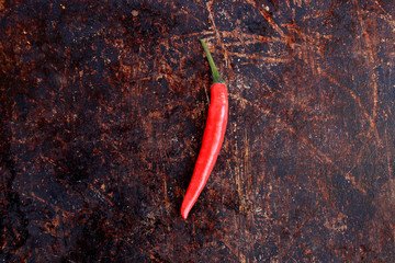 Single red thai chili pepper on brown rustic background