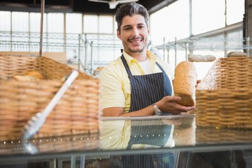 Smiling worker showing a loaf