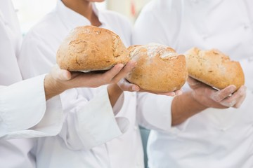 Colleagues holding loaf of bread together