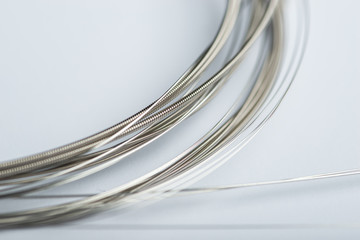 Electric guitar strings on white surface