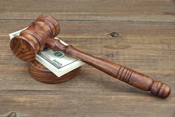Judges Gavel and Money Wad on Grunge Wood Table