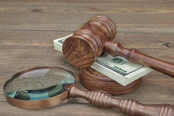 Gavel, Sounboard, Magnifier and Money Wad on Grunge Wood Table