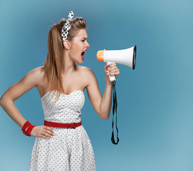 Nervous pin-up girl screaming with megaphone, speaking trumpet