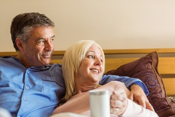 Happy mature couple smiling on bed
