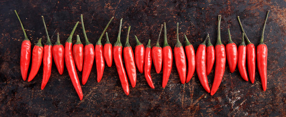 Row of red thai chili peppers on brown rustic background