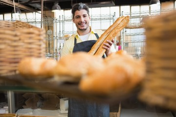 Cheerful waiter holding two baguettes