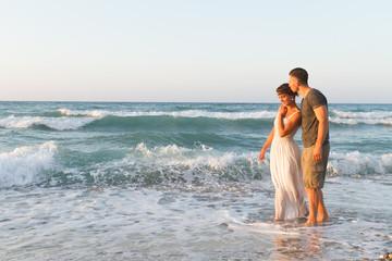 Young couple enjoys walking on a hazy beach at dusk.