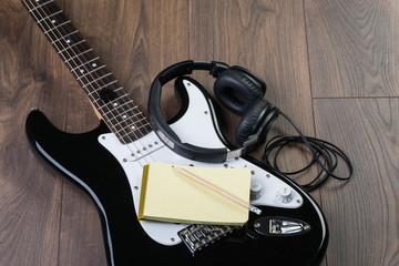 Electric guitar with headphones, notedpad and pencil