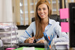 Brunette woman is working at the desk in the office