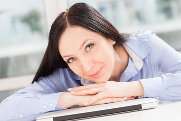 Brunette smiling businesswoman with notebook on the table is loo