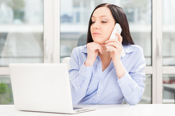 Brunette businesswoman is phoning while looking to the notebook