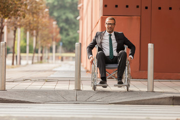 Businessman on wheelchair is trying to cross the road