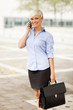 Portrait of blonde businesswoman standing outdoor with bag and p