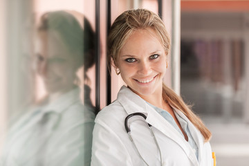 Portrait of smiling female doctor next to glass wall