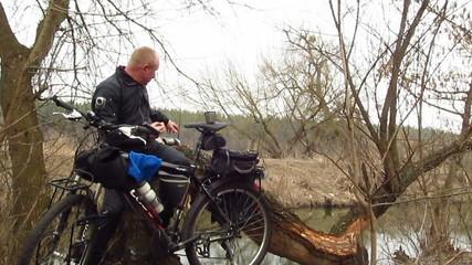 Adult  man  cyclist eats outdoors near river