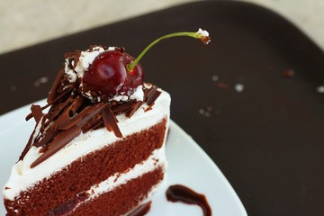 Chocolate cake with cherries on white dish.