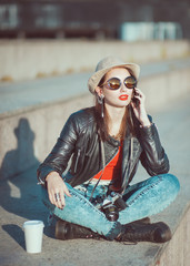 Hipster girl in leather jacket, hat with retro camera and mobile
