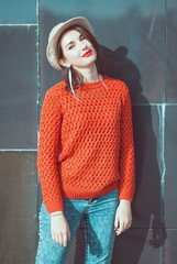 Young beautiful girl in red jersey and hat near wall