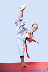 Girl on a gray background makes high leg kick