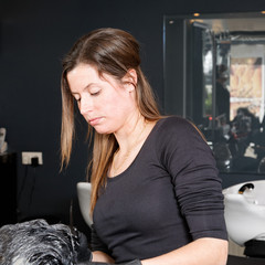 hairdresser colors hair with a brush