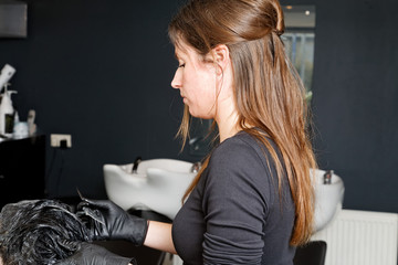 hairdresser is coloring the hair of a customer to black