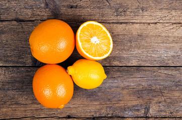 Fresh oranges and lemons on wooden background