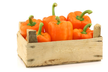 fresh orange bell peppers in a wooden crate on a white backgroun