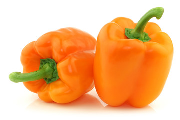 two fresh orange bell peppers on a white background