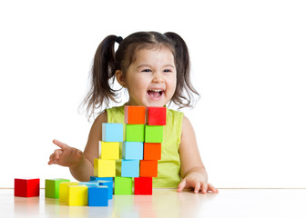 Beautiful kid building a castle with cubes