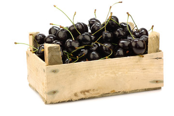 fresh delicious cherries in a wooden box on a white background