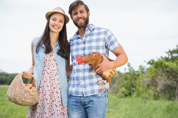 Happy farmers holding chicken and eggs