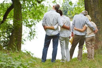Senioren mit Familie am Ufer vom See